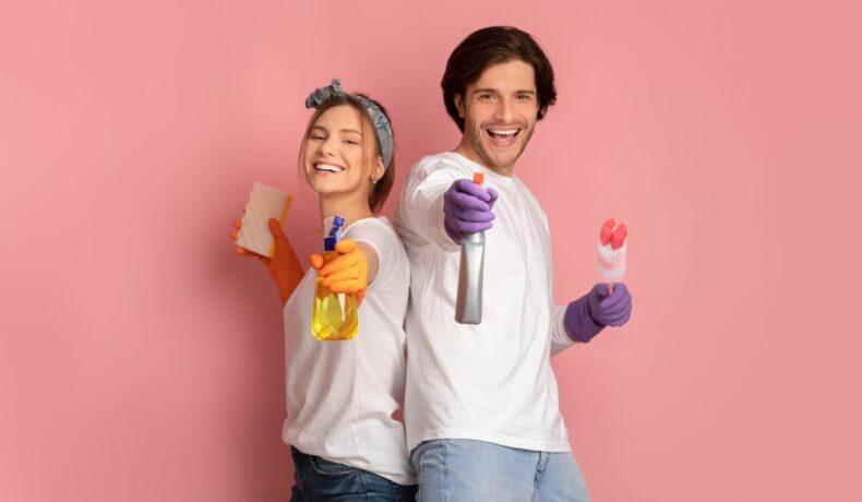 Un cuplu de tineri ce poartă mănuși de cauciuc mov și țin în mâini produse de curățenie, zâmbesc pe un fundal rozz