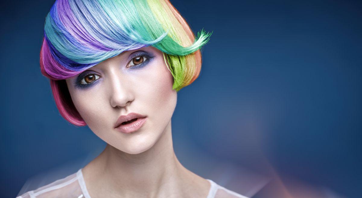 Tănără tunsă bob, cu breton și părul colorat în mai multe culori, pe fundal albastru