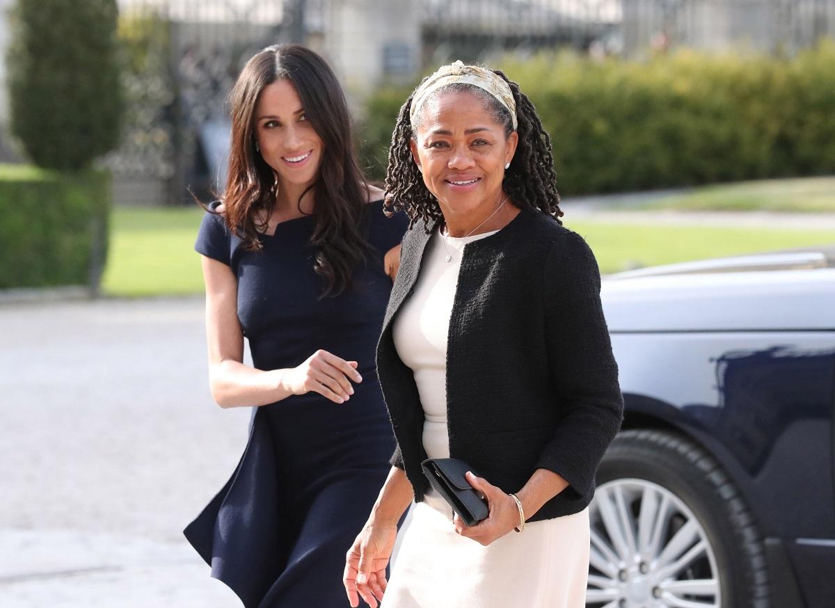 Doria Ragland, alături de fiica sa Meghan Markle, îmbrăcată într-o rochie albă cu un sacou negru, purtând o bentiță