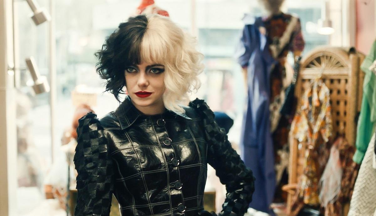 Emma Stone apare în lista de filme noi în Cruella îmbrăcată cu o bluză neagră de piele cu părul vopsit jumătate alb și jumătate negru