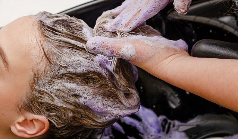 femeie care se spală pe păr cu șampon mov pentru a demonstra efectele acestuia
