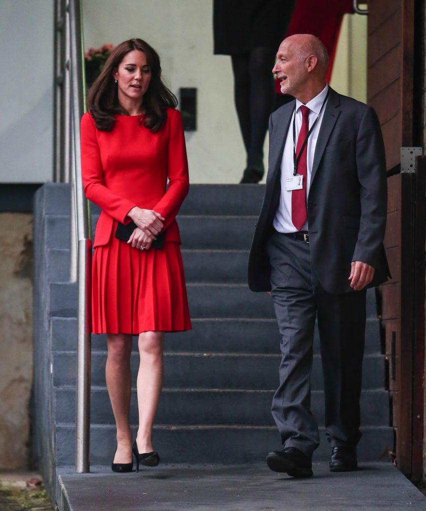 Printre alegerile vestimentare ale lui Kate Middleton este un costum roșu în timp ce coboară scările alături de un bărbat
