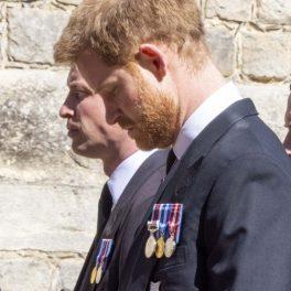 Prințul Harry și Prințul William, cu capul plecat, în timp ce mergeau în spatele sicriului bunicului lor