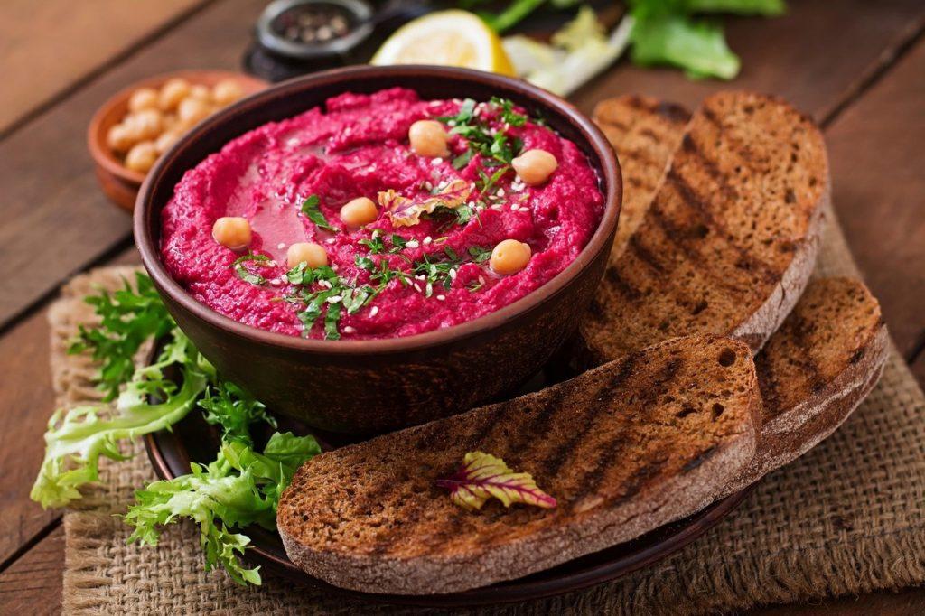 Hummus cu sfeclă roșie coaptă, în bol de ceramică, alături de pâine prăjită