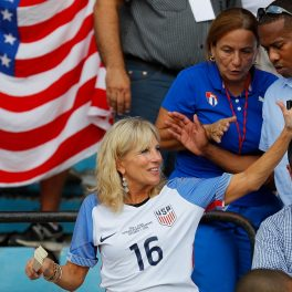Jill Biden, în tribună la meciul de fotbal dintre SUA și Cuba din anul 2016. Poartă un tricou al echipei de fotbal, niște cercei lungi albaștri și un set de brățări la mâna dreaptă.