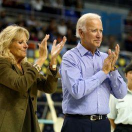 Jill Biden alături de Joe Biden. Amândoi aplaudă. Ea are părul pe spate și poartă o haină de culoare kaki. El are o cămașă albastru deschisși niște pantaloni negri.