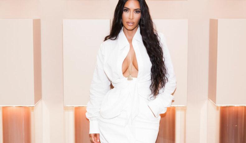 Kim Kardashian, la deschiderea unui magazin cu produse realizate de ea, îmbrăcată într-o rochie albă, cu decolteu adânc