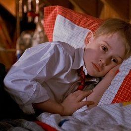 Macaulay Culkin, imagini din filmul Singur acasă, în timp ce stă în pat, trist