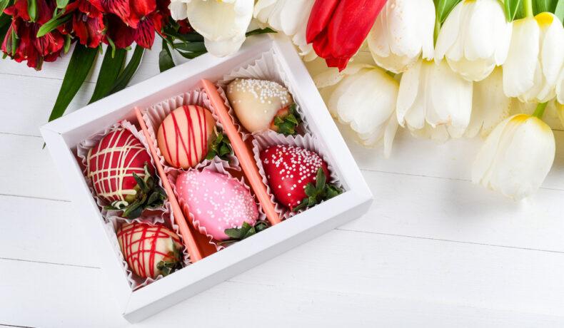 O cutie de bomboane, pe un fundal alb, cu lalele alături