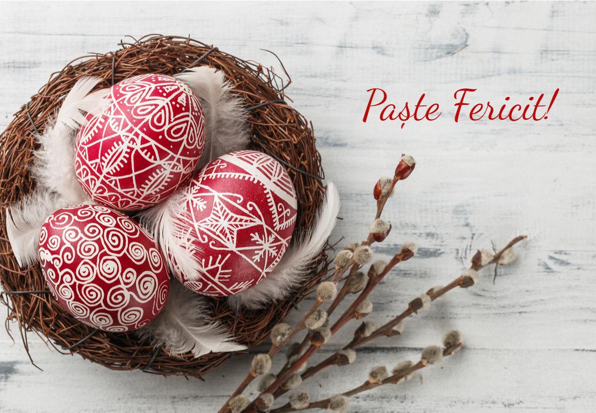 Un coș cu ouă roșii, cu mesajul Paște fericit