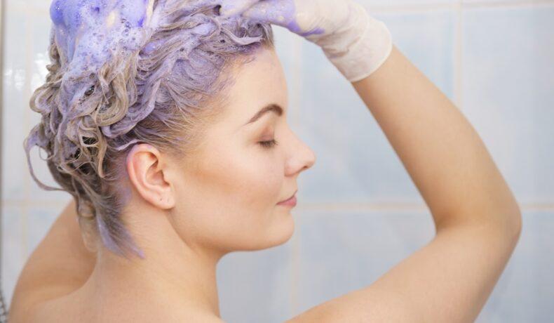 femeie care foloseste un șampon violet pentru a neutraliza tonurile de galben
