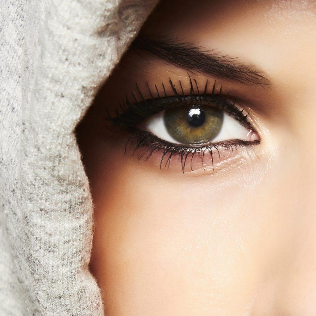 O femeie cu ochii verzi are aplicate gene false și ochii conturați cu un creion negru.I se vede doar un ochi ș o parte din gluga gri a hanoracului.