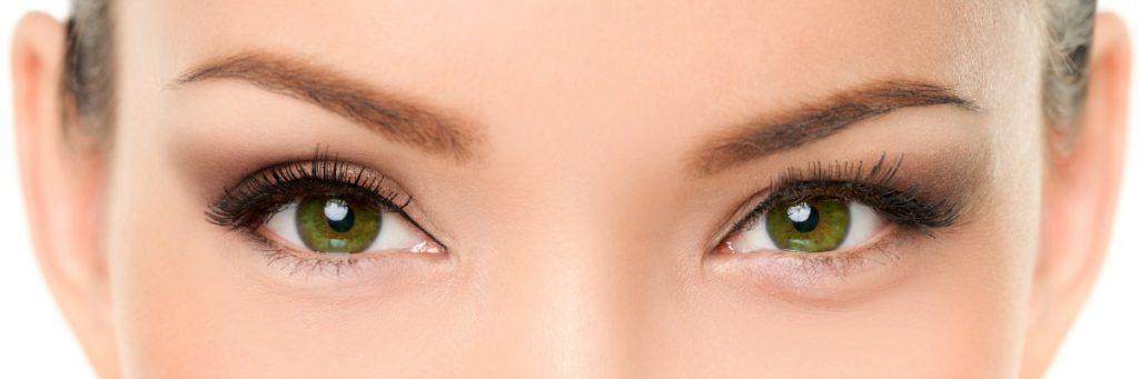 O femeie cu ochii verzi are gene false, sprâncene vopsite, se uită fix în poză.