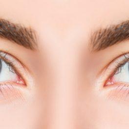 O femeie cu ochii albaștri are gene false aplicate discret și sprâncenele conturate sunt încadrate perfect în restul feței.
