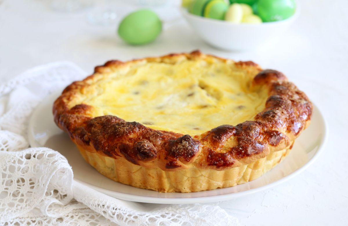 Pască cu aluat de cozonac, așezată pe o farfurie, aflată pe o masă alături de câteva ouă vopsite în culoarea verde.