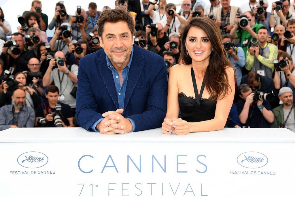 Penelope Cruz într-o rochie neagră alături de sățul ei Javier Bardem îmbrăcat într-un costum albastru în timp ce stau la un pupitru de la festivalul internațional de film Cannes