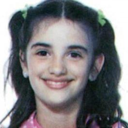Penelope Cruz care zâmbește larg în copilărie cu două codițe prinse cu elastic verde