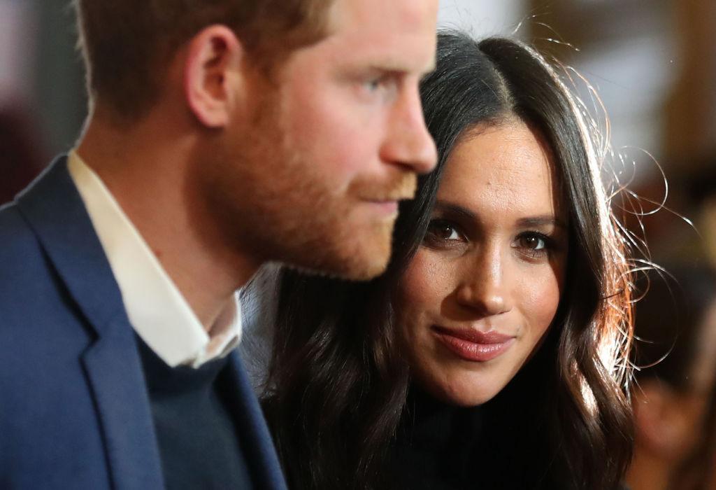 Prinul Harry, alături de Meghan Markle, în vizită la Edinburgh, în anul 2018, fotografiați în timp ce Meghan privește profund spre soțul ei