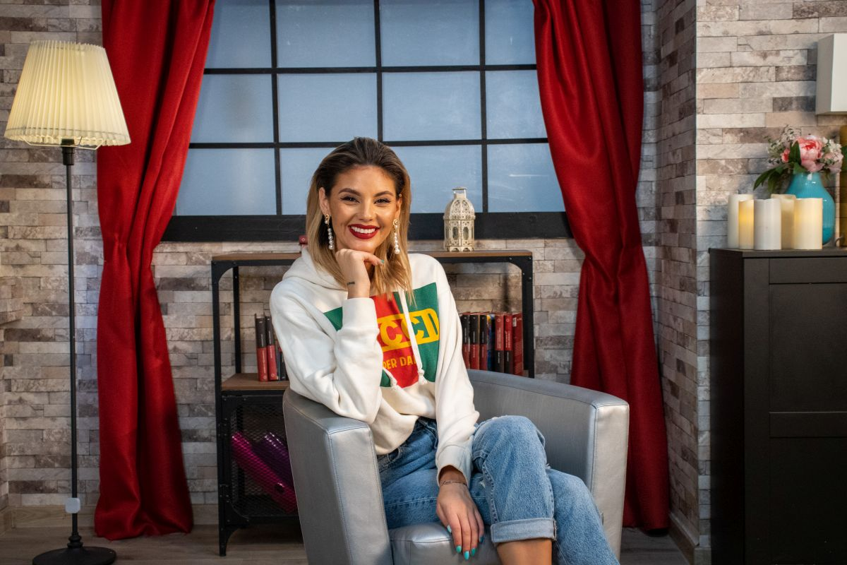 Ramona Olaru, tânără, frumoasă și mereu sinceră, zâmbește la cameră, în timp ce stă pe un scaun în studioul unde sunt filmate interviurile din seria CaTine.ro..