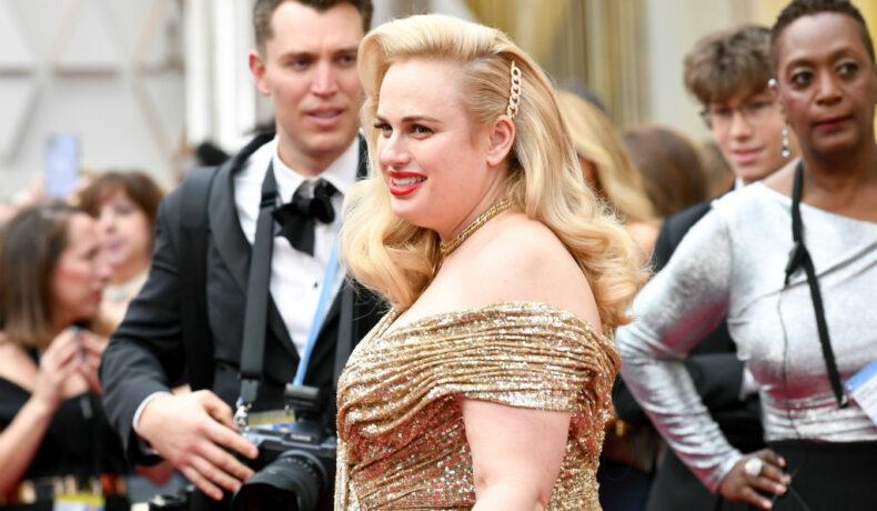 Rebel Wilson, la Premiile Oscar 2020, pe covorul roșu, într-o rochie aurie
