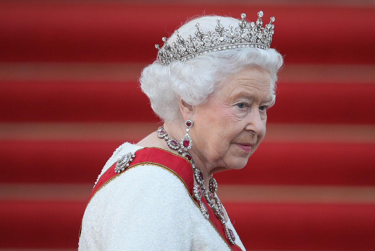 Regina Elisabeta purtând o tiara și un set de bijuterii îmbrăcată într-un costum alb la un banchet din Berlin
