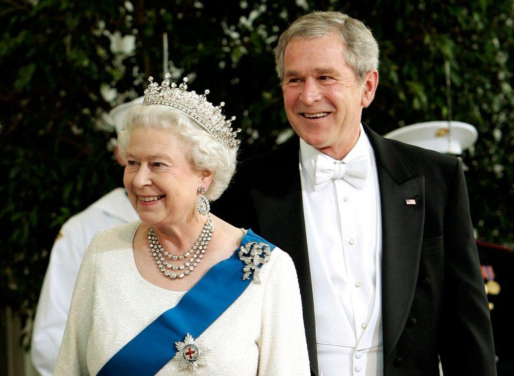 regina elisabeta într-un costum alb purtând o diademă și broșa reginei Maria alături de președintele Bush îmbrăcat într-un costum negru