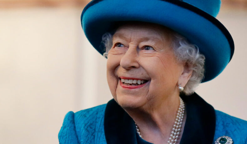 Regina Elisabeta, într-un costum albastru, zâmbitoare, într-o vizită regală
