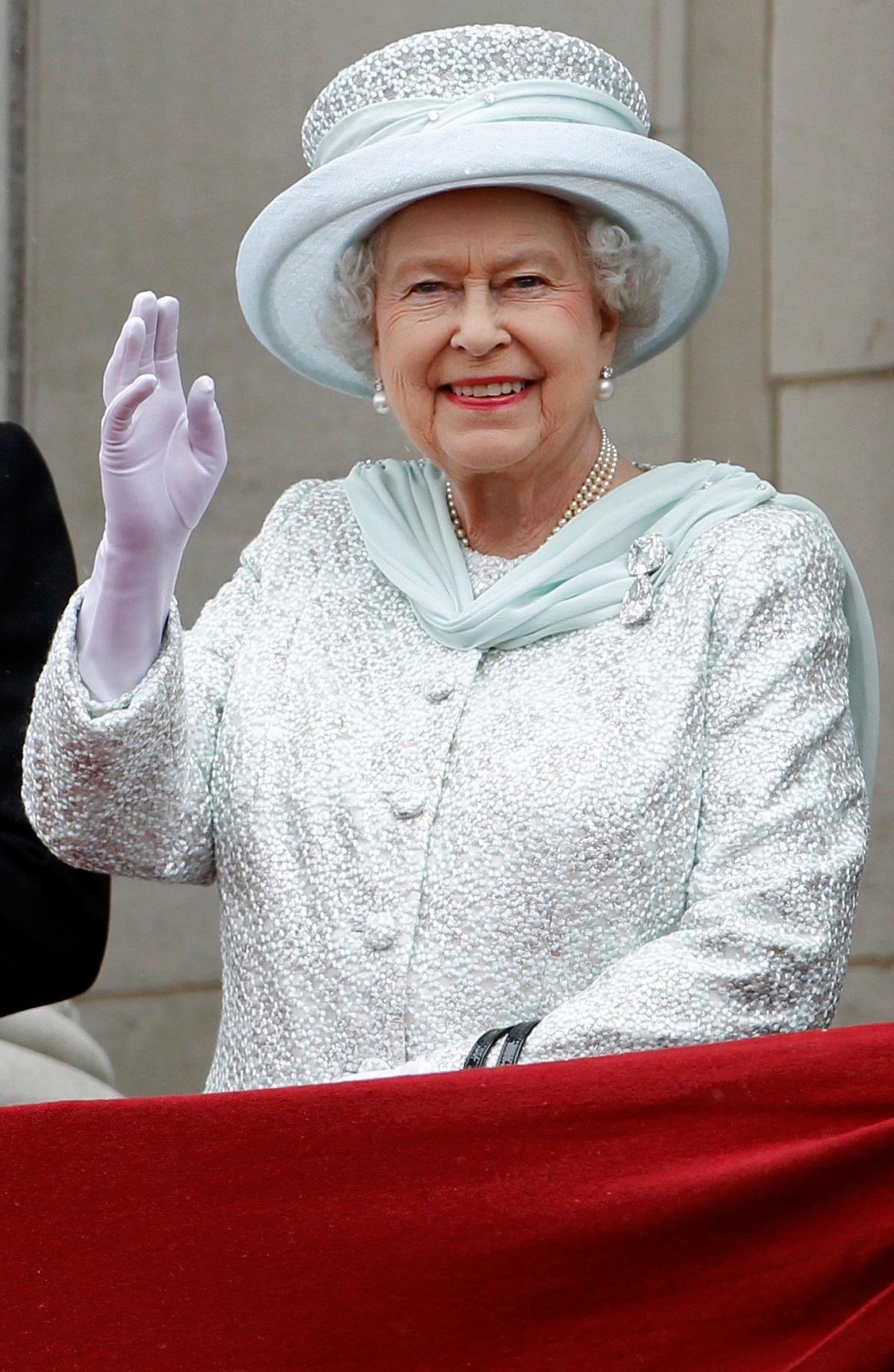 regina Elisabeta curtând pălărie albă și costum alb în timp ce face cu mâna oamenilor, iar în piept poartă diamantele Cullian