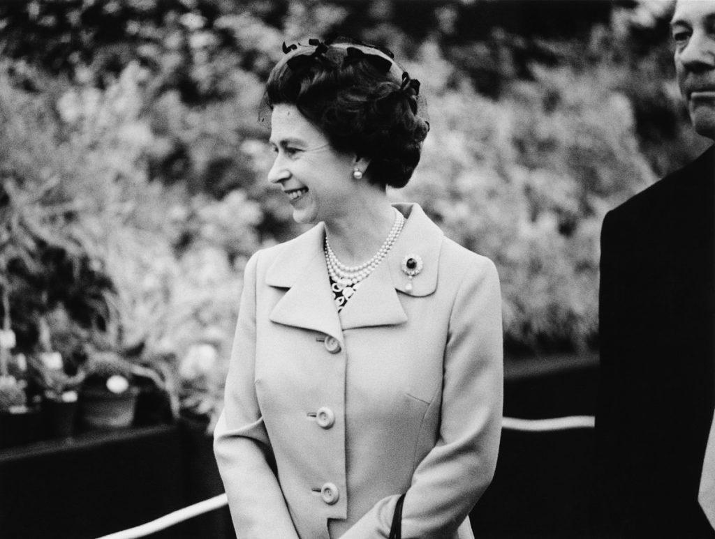 regina elisabeta într-o ținută elegantă în tinerețe purtând în piept broșa sa cu safir