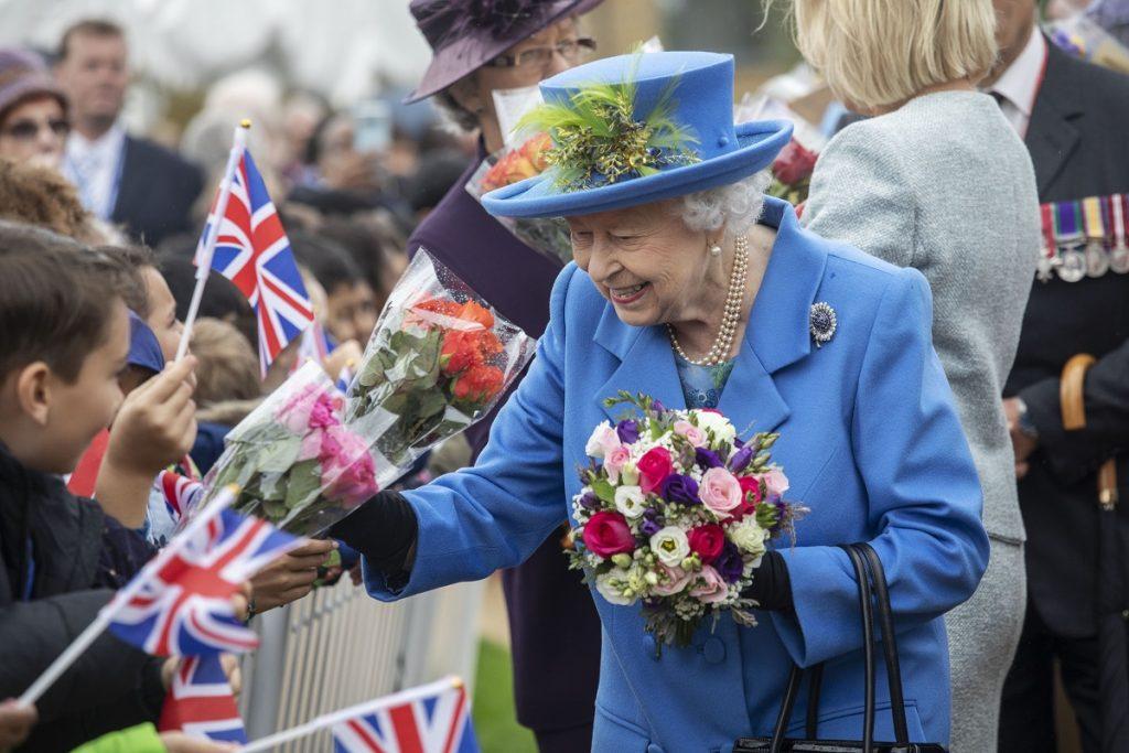 regina elisabeta într-un costum albastru cu pălărie primid flori de la copii și purtând în piept brășa sa cu safir