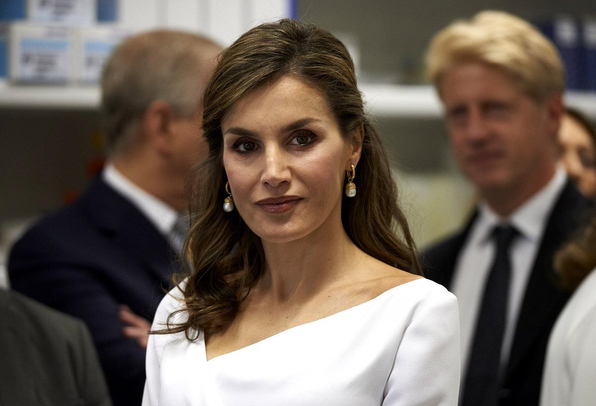 Portretul Reginei Letizia a Spaniei într-o vizită oficială, purtând o bluză elegantă albă și o pereche de cercei tip perluțe