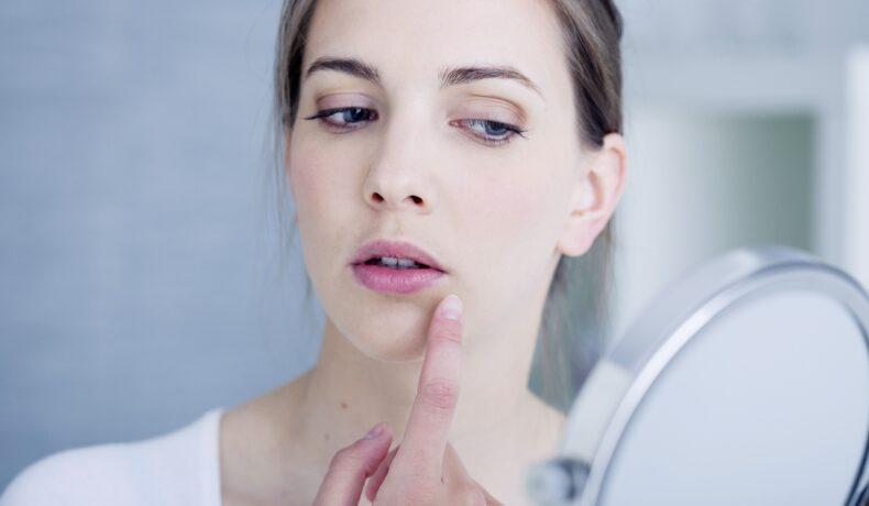 O femeie cu buze crăpate are părul strâns la spate, se privește într-o oglindă rotundă