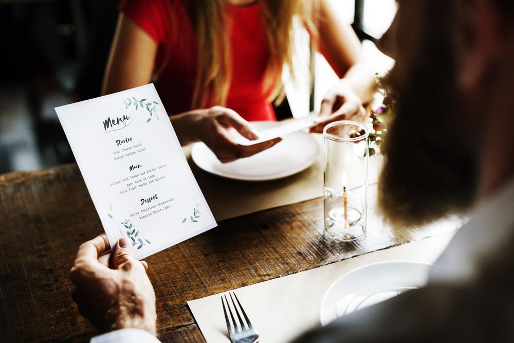 Doi tineri care se află la masă, la restaurant, în timp ce se uită pe meniu