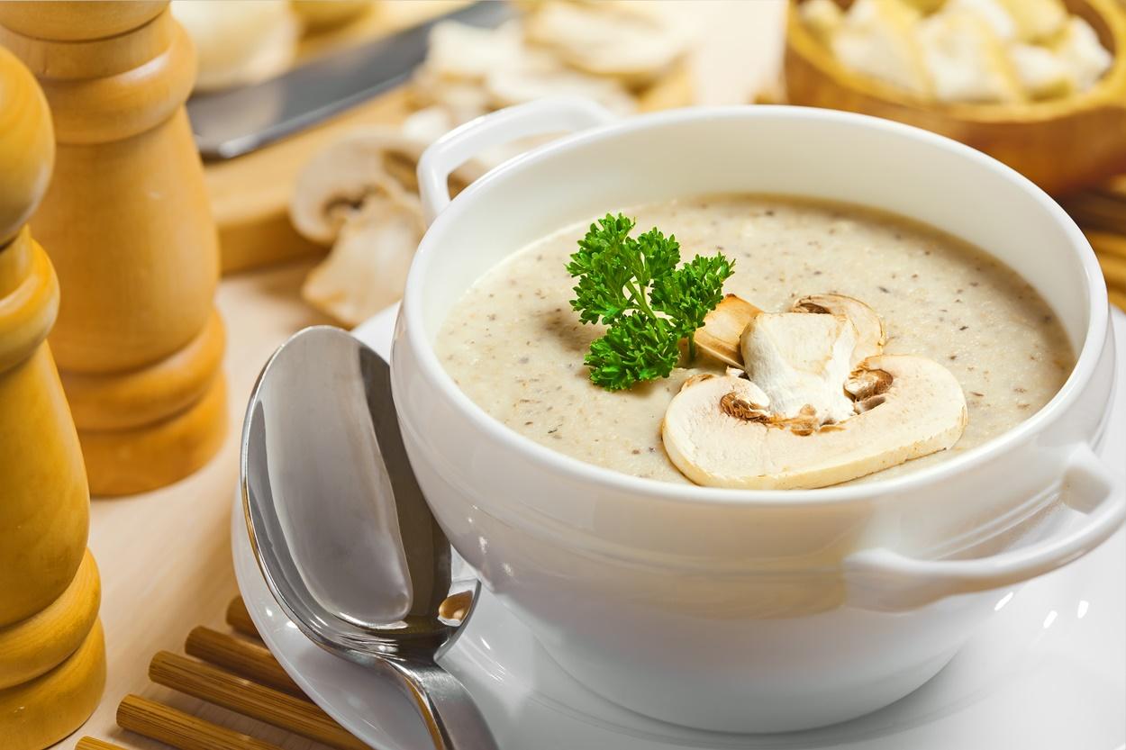 Supă cremă de ciuperci cu lapte de cocos servită într-un bol alb