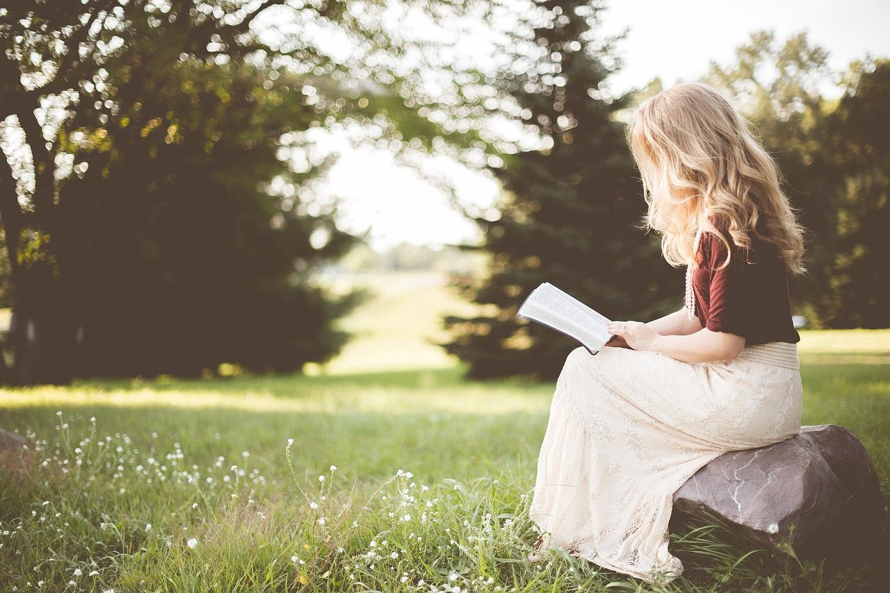 O femeie care stă în iarbă și citește