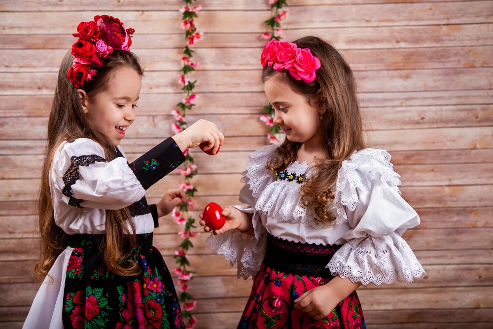Două fetițe, îmbrăcate în costum tradițional, în timp ce ciocnesc ouă roșii