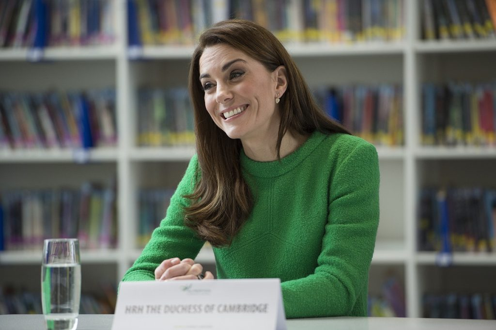 Alegerea vestimentară a lui Kate Middleton într-un portret cu ea la un birou purtând un pulover verde și zâmbind publicului