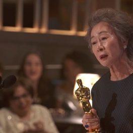 Yuh Jung Youn, îmbăcată într-o rochie închisă la culoare, ține în mână o statuetă Oscar la gala organizată în anul 2021.
