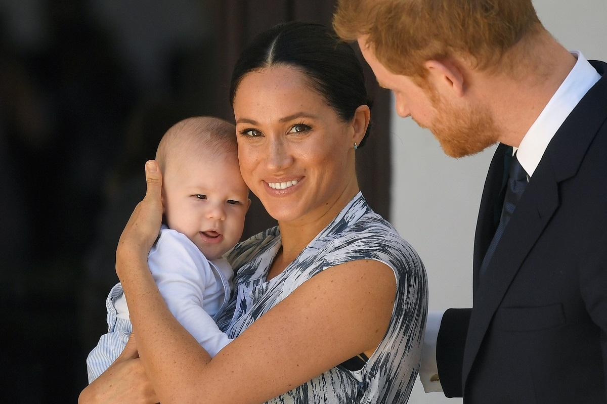 Fiul Ducilor de Sussex într-un body alb în timp ce este ținut într-un mod protector de mama sa, Meghan Markle, în brațe iar Prințul Harry îi privește admirativ în călătoria pe care au făcut-o în 2019 în Africa de Sud