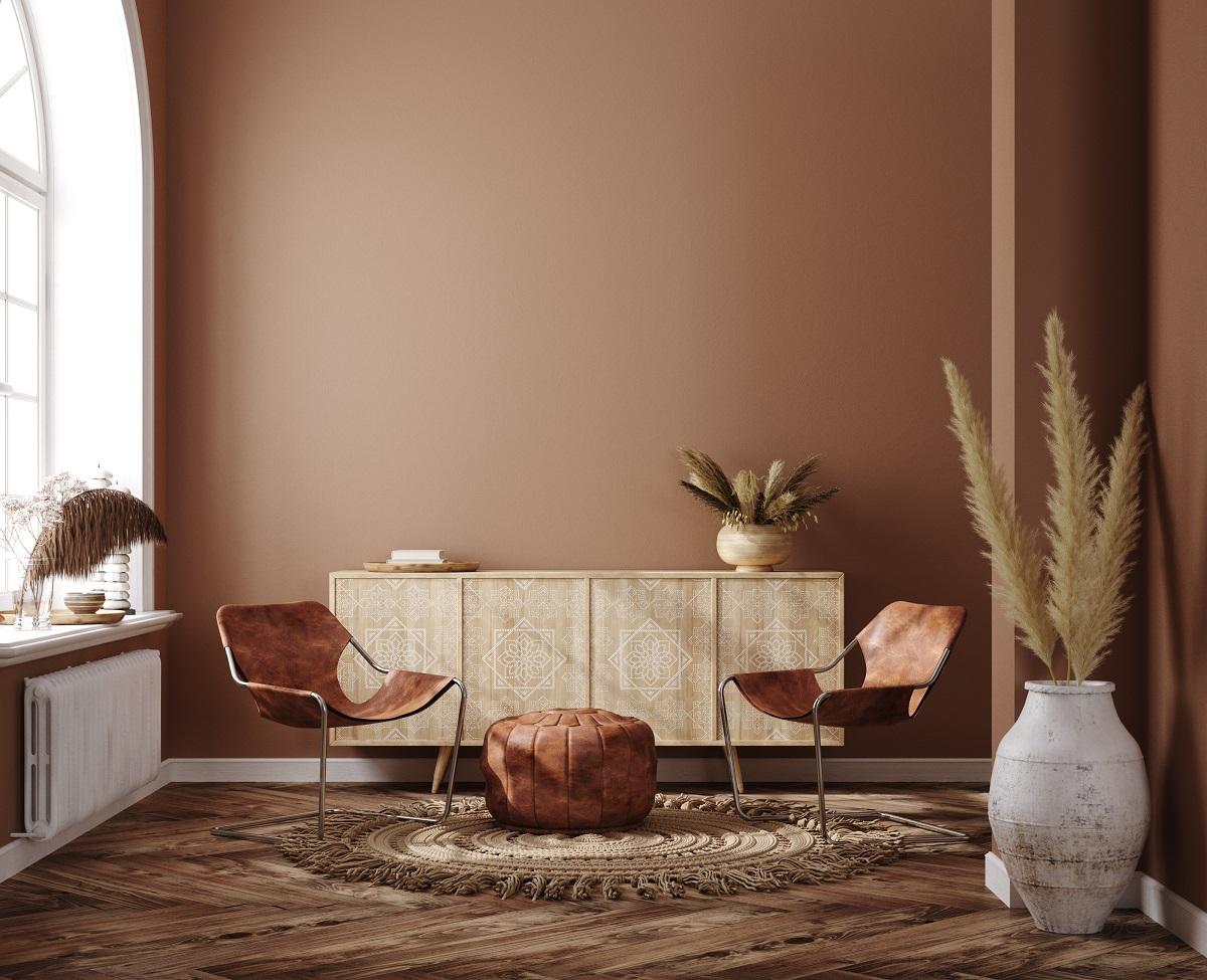 o încăpere cu pereți vopsiți în nuanțe de maro cu o fereastră largă un covor rotund, o masă și un scaun mic alături de câteva vaze umplute cu stuf pentru a demonstra cum să folosești câteva trucuri simple de design interior