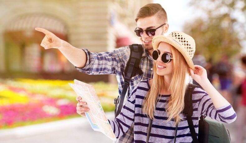 O tânără cu pălărie și ochelari de soare alături de prietenul său care îi arată una dintre cele cinci destinații sigure pentru vacanță, în timp ce tânăra ține în mână harta pe care o verifică