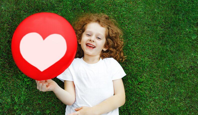 Fetiță în tricoul alb care stă ăntinsă pe iarbă în timp ce face una din acele activități creative de 1 iunie și ține în mână un balon roșu cu inimioară