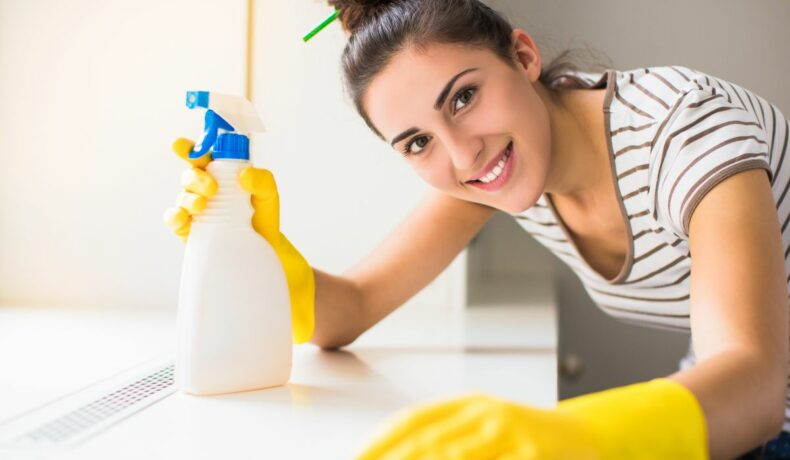 O tânără ce poartă mănuși galbene de latex, și are în mână un spray, curăță pervazul