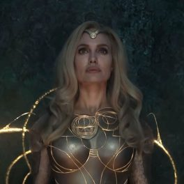 Angelina Jolie îmbrăcată la fel ca zeița Thena în rolul din filmul Eternals în timp ce își concentrează puterile pentru a face arme din energiile cosmice