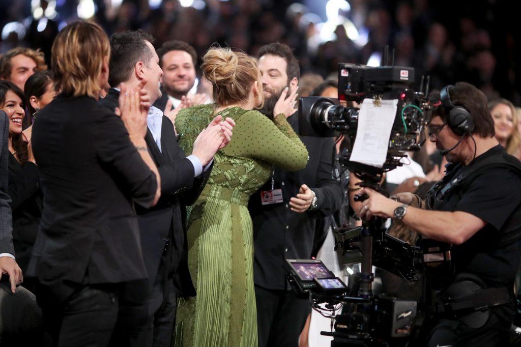 Adele la gala Premiilor Grammy îmbrăcată într-o rochie verde lungă în timp ce își sărută soțul și este aplaudată de public