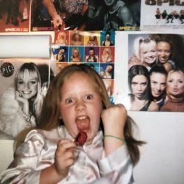 Adele în copilărie îmbrăcată într-o bluzită albă în timp ce ține în mână o căpșună și se preface că sunsține un concert