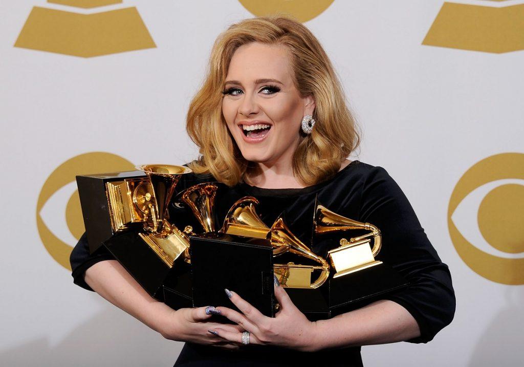 Adele la Premiile Grammy din 2012 zâmbind la public în timp ce ține în brațe cele șase statuete pe care le-a câștigat