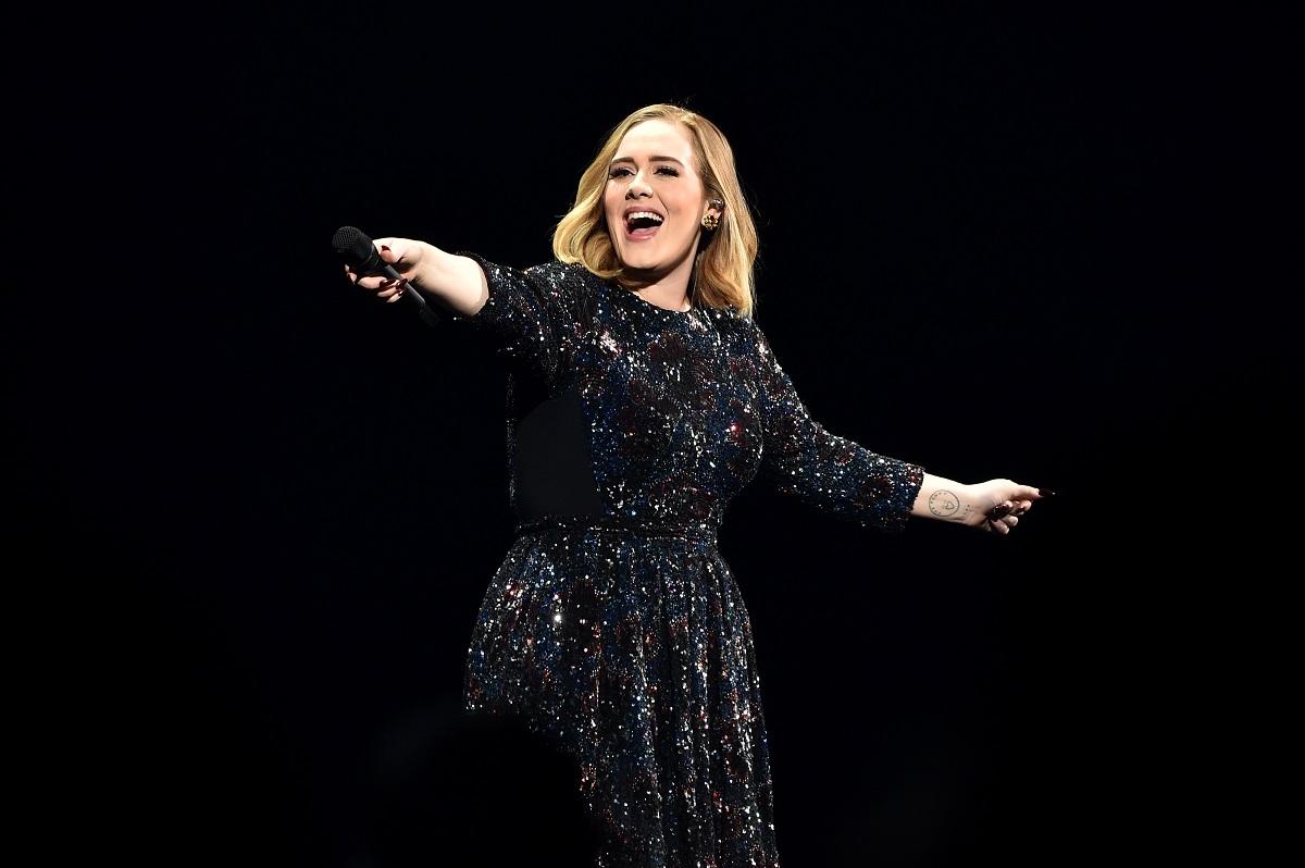 Adele pe scenă îmbrăcată într-o rochie albastră cu paiete în timp ce zâmbește și îndreaptă microfonul către public