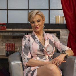 Nutriționista Anca Alungulesei pozând picior peste picior într-o rochie violet cu imprimeu gri în timp ce zâmbește prietenos pentru interviul CaTine.ro