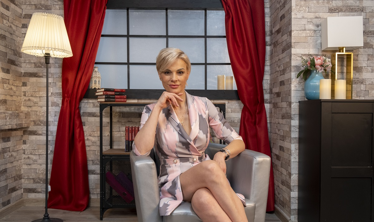 Anca Alungulesei îmbrăcată într-o rochie vaporoasă de culoare violet, ținând mâna dreaptă sub bărbie și zâmbind la cameră la interviul pentru CaTine.ro